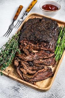 양지머리 바베큐 쇠고기 고기는 나무 쟁반에 얇게 썰어져 있습니다. 흰 바탕. 평면도.