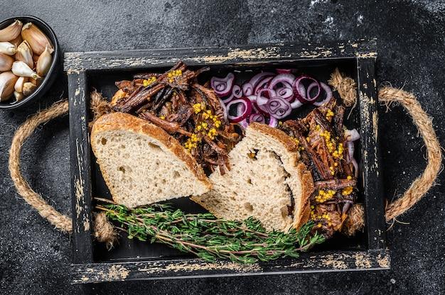 나무 쟁반에 훈제 쇠고기 고기를 넣은 양지머리 샌드위치. 검은 배경. 평면도.