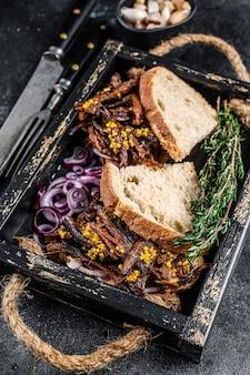 Сэндвич с грудинкой с копченой говядиной на деревянном подносе