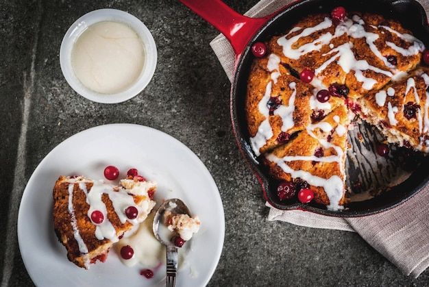 British english traditional pastries. cookies pie cranberry scones with orange peel, with sweet white glaze, in a frying pan and on a plate