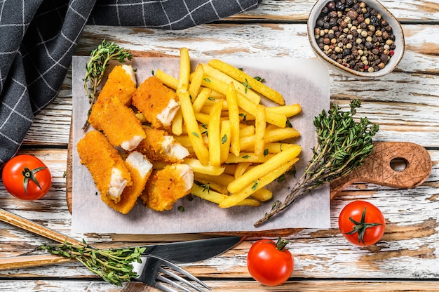 British fish and chips on white wooden table.