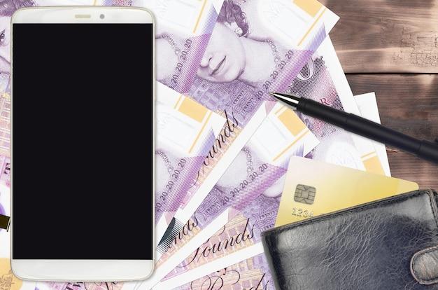 英国ポンド紙幣と財布とクレジットカード付きのスマートフォン
