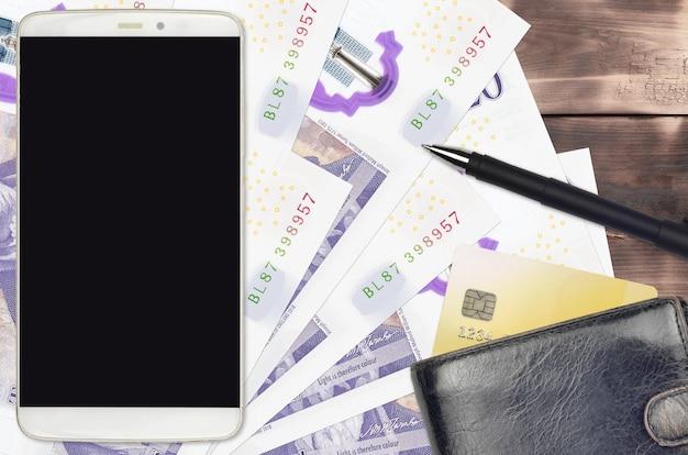 英ポンドの紙幣と財布とクレジットカード付きのスマートフォン
