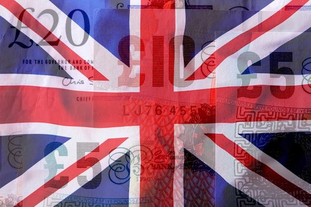 바람에 날리는 영국 유니온 잭 깃발. 영국 국기는 화려하고 배경은 파운드 지폐입니다.