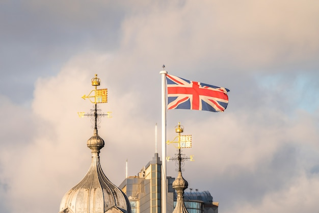 Британская волна колышется в небе с флюгером на церкви