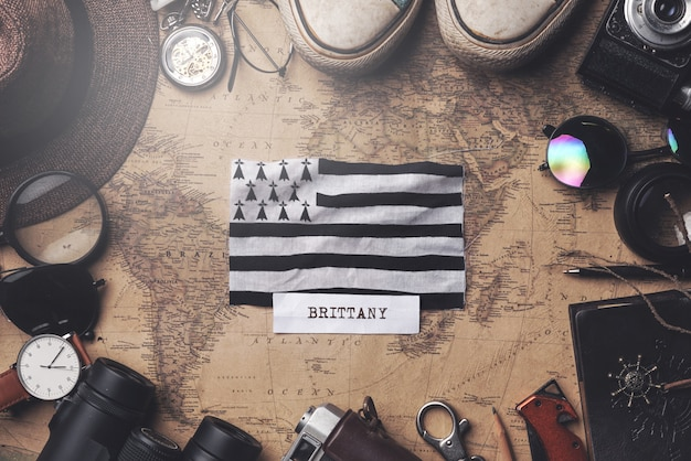 Brittany flag between traveler's accessories on old vintage map. overhead shot