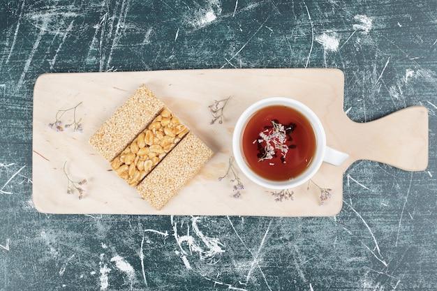 木の板に脆いキャンディーとお茶。高品質の写真