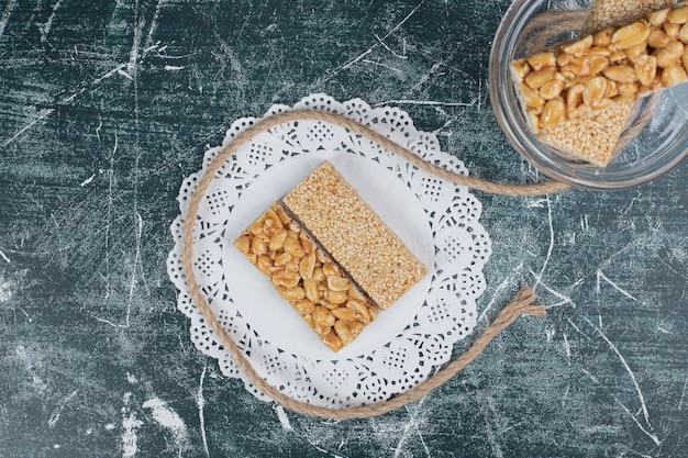 ロープで大理石の背景に種子とナッツの脆いキャンディー。高品質の写真