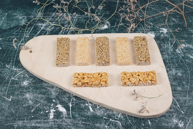 Хрупкие конфеты с семенами и орехами на деревянной доске.