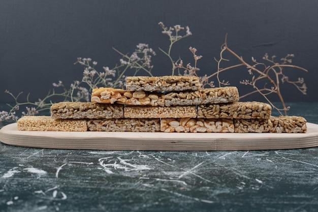Хрупкие конфеты с семенами на деревянной тарелке.