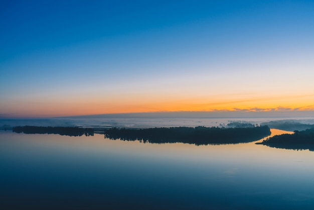 Broad river flows along diagonal shore with forest under thick fog. early blue sky reflected in water. yellow glow in picturesque predawn sky.