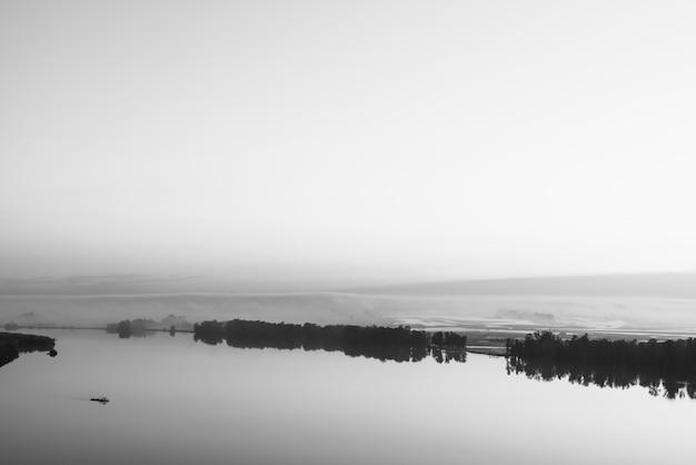 Широкая река течет вдоль диагонального берега с силуэтом леса и густого тумана в оттенках серого.