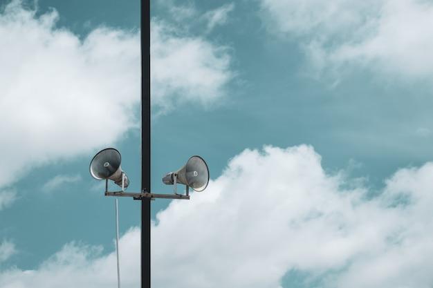Broadcast speaker for public relation. vintage horn speaker over blue sky with clouds.