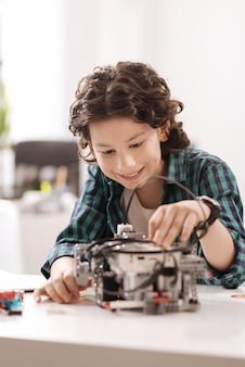 Расширяю кругозор. способный веселый вовлеченный мальчик сидит в классе и работает с электронными гаджетами, одновременно учится и выражает радость.