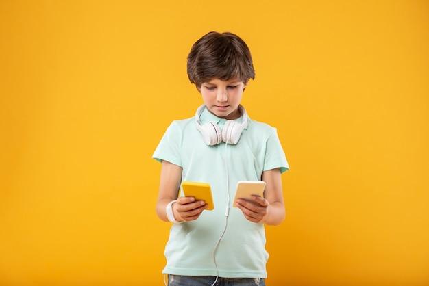 心を広げる。 2つの電話を持ち、ヘッドフォンを身に着けている深刻なハンサムな男の子