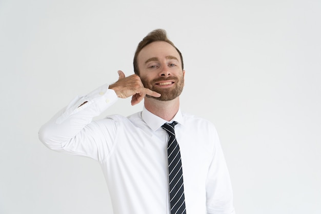 Broadly smiling businessman asking by gesture to phone him.
