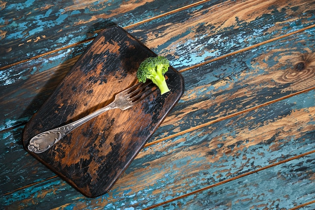 Broccoli on antique fork on burned-out kitchen board on rough dyed wooden blue table.
