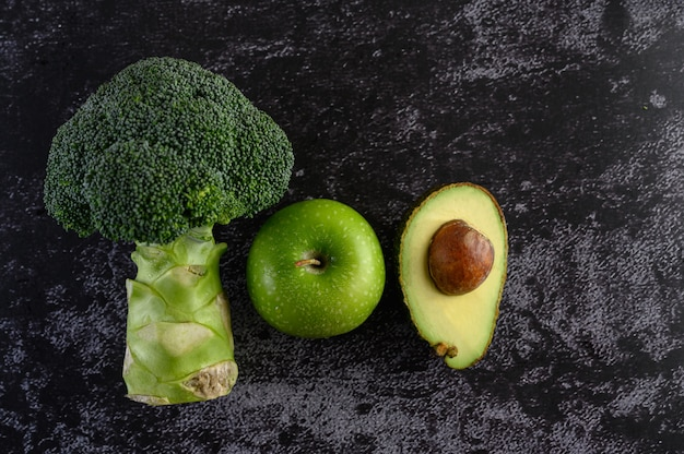 Broccoli, apple, and avocado on a black cement floor.