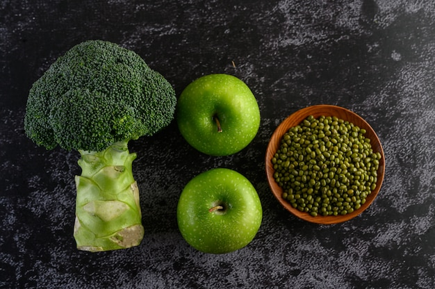 Broccoli, apple, and mung bean on a black cement floor.