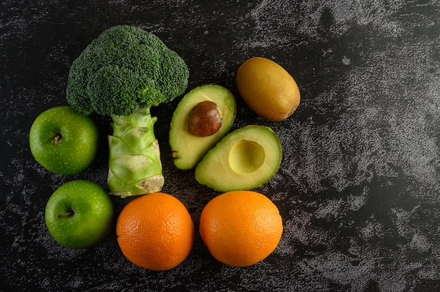 Broccoli, apple, orange, kiwi, and avocado on a black cement floor.