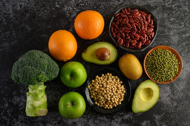 Broccoli, apple, orange, kiwi, legumes, and avocado on a black cement floor.