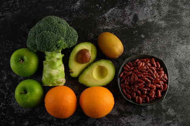 Broccoli, apple, orange, kiwi, red bean, and avocado on a black cement floor.