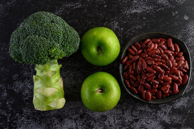 Broccoli, apple, and red beans on a black cement floor.