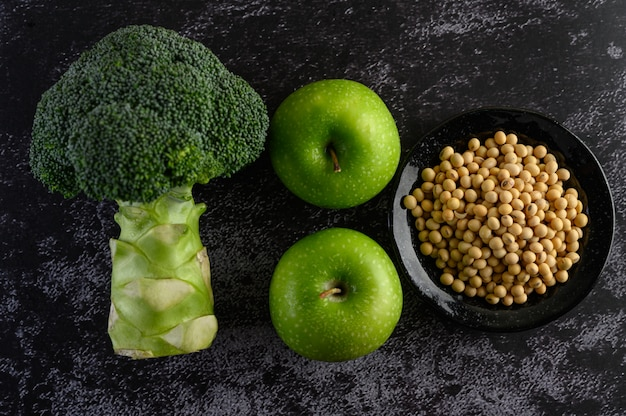 Broccoli, apple, and soy beans on a black cement floor.