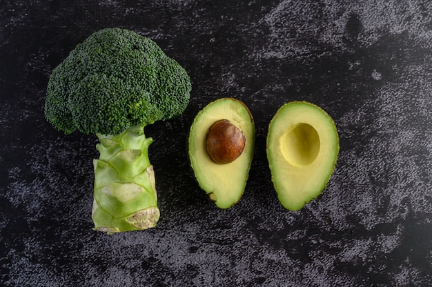 Broccoli and avocado on a black cement floor.
