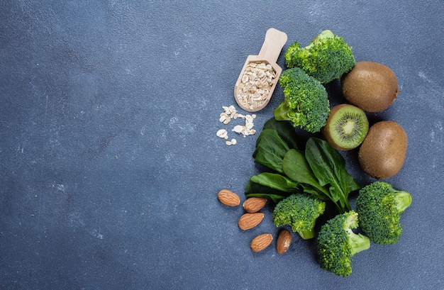 Broccoli, avocado, spinach, kiwi, oats and almond on blue concrete stone table background. top view