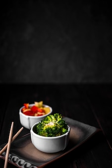Broccoli and bell pepper in cups with chopsticks