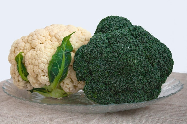 Broccoli and cauliflower are on the table in a transparent plate. the concept of proper nutrition