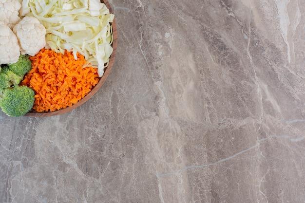 Брокколи, цветная капуста, капуста и морковь нарезанные на большом деревянном подносе на мраморе.