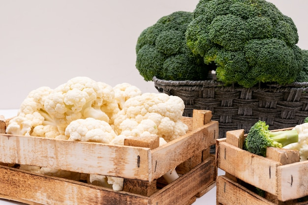 Broccoli and cauliflower in wooden box and broccoli in basket