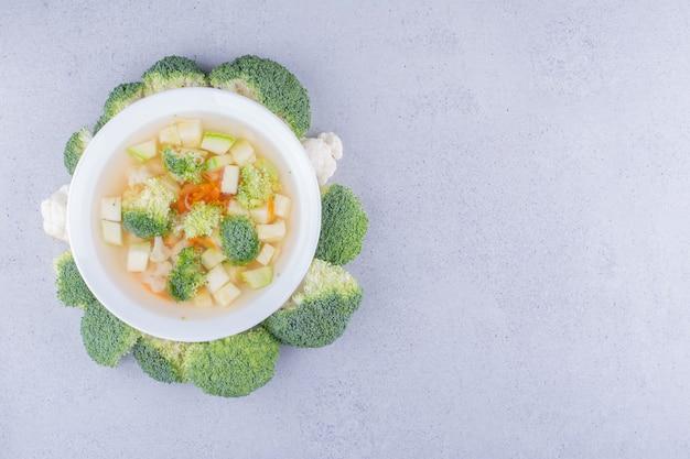 Cerchio di broccoli attorno a una porzione di insalata di verdure su fondo marmo. foto di alta qualità