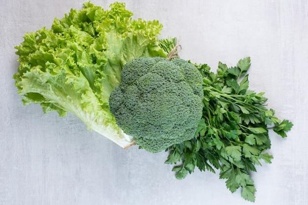 Broccoli, foglie di coriandolo e lattuga sulla superficie della pietra. foto di alta qualità