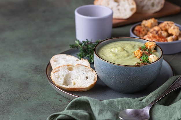 Broccoli cream soup decorated with thyme, cream, roasted cauliflower and fresh bread.