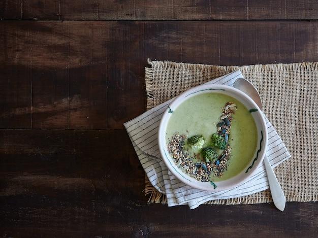 그릇에 먹을 준비가 된 위에 씨앗을 곁들인 브로콜리 크림 수프