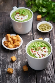 Broccoli cream soup. vegetable green puree in cup. diet vegan soup of broccoli on dark