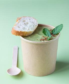 공예 용기에 빵, 민트, 향신료가 들어간 브로콜리 크림 수프. 갈 수프, 건강한 음식 배달.