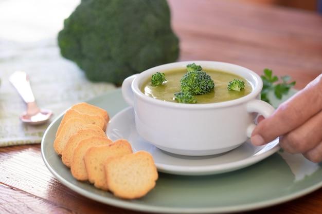健康的な食事のための木製のテーブルにクルトンとブロッコリークリームスープ