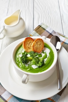 Broccoli cream soup with fresh mint in a white soup bowl served with toasted slices of baguette and fresh cream, vertical view from above