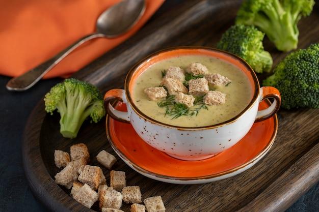 채소와 나무 테이블에 크래커와 브로콜리 크림 수프. 비타민, 미량 원소 및 섬유질이 풍부한 건강 식품. 채식주의 자 음식.