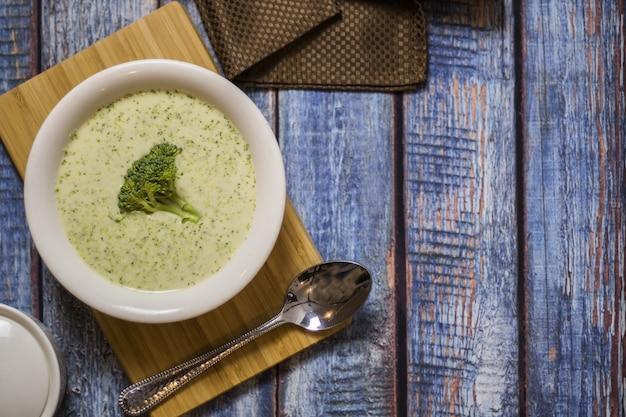 Piatto di crema di broccoli su un tavolo di legno blu