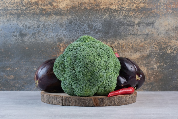 Broccoli, eggplants and peppers on wooden piece. high quality photo