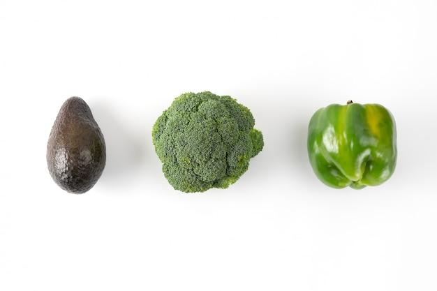 Брокколи, зеленый перец, авокадо. овощной креативный макет на зеленом фоне