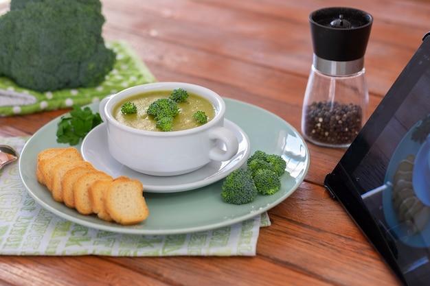 ブロッコリー。タブレットのレシピに従ったクルトン入りブロッコリーの自家製クリームスープ。カロリーなしでビタミンを使った健康的な食事。健康的な栄養の概念。木製の背景
