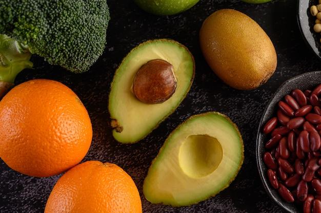 Broccoli, arance, kiwi, avocado e fagioli rossi su un pavimento di cemento nero.