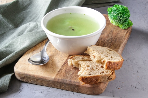 나무 배경 위에 하얀 접시에 브로콜리 수프입니다. 건강한 다이어트 식품.