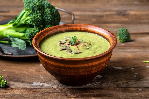 木製の背景のボウルにブロッコリースープ。緑の野菜のビーガンスープピューレ